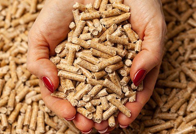 Zwei Hände greifen in eine Menge von Holz Pellets