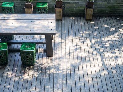 Holzterrasse mit Stühlen Tisch und Pflanzen